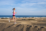 Young woman jogging on the beach - DIGF000001
