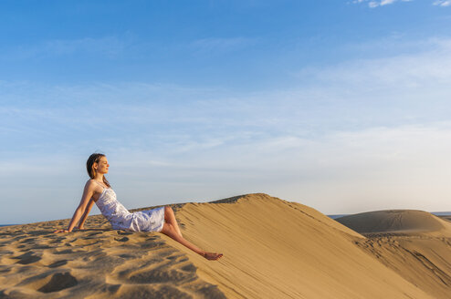 Woman sitting on dune, contemplating - DIGF000013