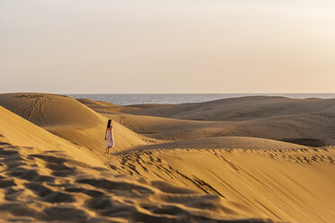 Woman walking over sand dunes - DIGF000019