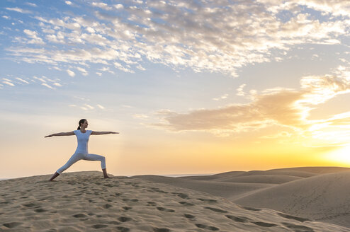 Woman practising yoga on sand dunes - DIGF000025