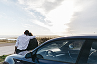 Spain, Cubelles, back view of a young couple sitting on the hood of the car watching the sea at sunset - JRFF000351