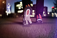 Sneakers of jogging man on tarmac at night - RBF004069