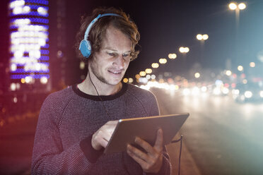 Germany, Munich, portrait of man with headphones using digital tablet at night - RBF004072