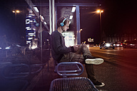 Germany, Munich, man with headphones sitting at bus stop using digital tablet at night - RBF004075