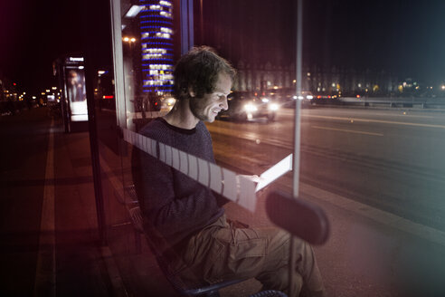 Germany, Munich, man with headphones sitting at bus stop using digital tablet at night - RBF004078
