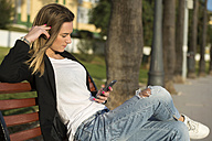 Spain, Puerto Real, woman sitting on a bench looking at smartphone - KIJF000124
