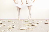 Ballet shoes scattered on the floor with two dancers in the background - MRAF000004