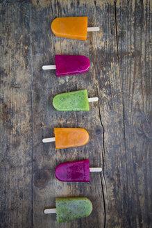 Row of fruit smoothie ice lollies on dark wood - LVF004455