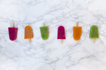 Row of fruit smoothie ice lollies on white marble - LVF004461