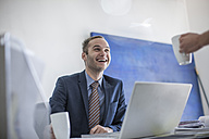 Laughing businessman at desk with cup of coffee looking at colleague - ZEF007964