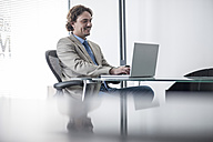 Smiling businessman at desk with laptop - ZEF007985