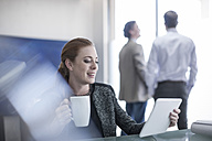 Smiling woman in office holding cup of coffee and digital tablet - ZEF007994