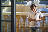 Boy listening music with headphones and smartphone on balcony - SIPF000124