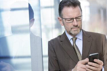 Portrait of businessman with spectacles using smartphone - GUFF000246