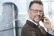 Portrait of smiling businessman telephoning with smartphone - GUFF000249