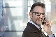 Portrait of smiling businessman telephoning with smartphone - GUFF000252