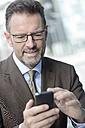 Portrait of businessman with spectacles using smartphone - GUFF000255