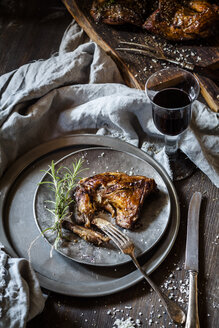 Rabbit legs on plate, thyme, rosemary and sea salt, red wine glass - SBDF002647