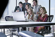 Business people celebrating success in office, looking at laptop - ZEF008016