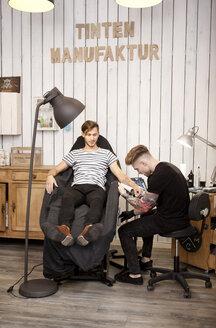 Tattooist at work in his tattoo studio - MFRF000486