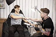 Tattooist and client giving fist bump after work is done - MFRF000498