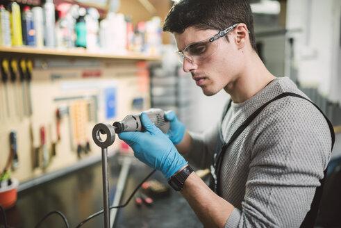 Young mechanic working in repair garage - RAEF000791