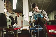 Young mechanic working in repair garage - RAEF000797