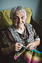 Portrait of smiling senior woman with  knitting - RAEF000810