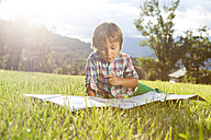 Spain, Cerdanya, little boy on a meadow looking at map - VABF000077
