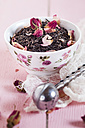 Bowl of black tea with dried rose blossoms - SBDF002663