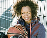 Portrait of smiling young woman with basketball - MADF000776