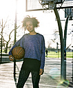 Portrait of young woman with basketball at backlight - MADF000779