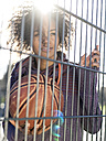 Portrait of young woman with basketball standing behind a fence - MADF000785