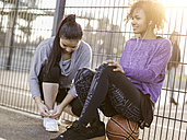 Two young women with on a streetball field - MADF000788