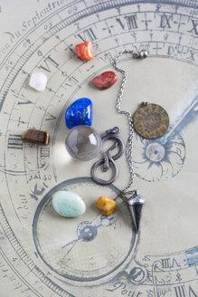 Semiprecious stones, pendulum, pendant and crystal ball on horoscope circle - MYF001325