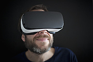 Smiling man wearing Virtual Reality Glasses - RBF004085