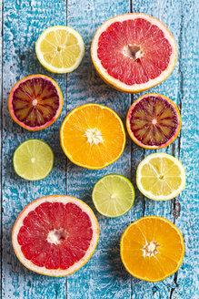 Sliced citrus fruits on light blue wood - SARF002491