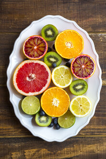 Plate of blueberries, kiwis and sliced citrus fruits on wood - SARF002494