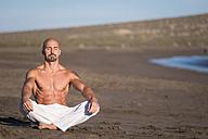 Spain, Tenerife, man meditating on the beach - SIPF000141