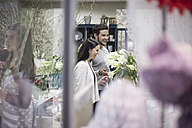 Smiling young man and woman in flower shop - ZEF008112