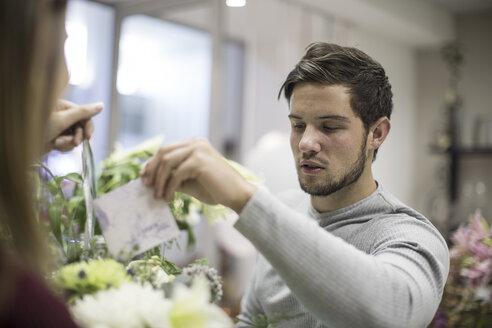 Man putting greeting card in flower arrangement - ZEF008124