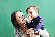 Portrait of happy mother with her little son in front of green background - GEMF000663