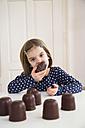 Portrait of little girl eating chocolate marshmallow - LVF004486