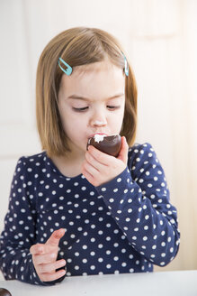 Portrait of little girl eating chocolate marshmallow - LVF004489