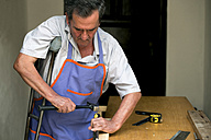 Senior man with crutch working at workbench - KIJF000133