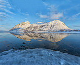 Norway, Mountain reflected in a frozen lake at sunset - LOMF000190