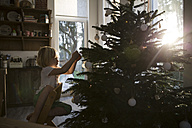 Girl decorating Christmas tree in backlight - FKF001672