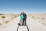 Bolivia, Uyuni train cemetery, couple kissing on the railway - GEMF000666