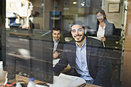 Group of people working at office near to window with young man smiling - JASF000355