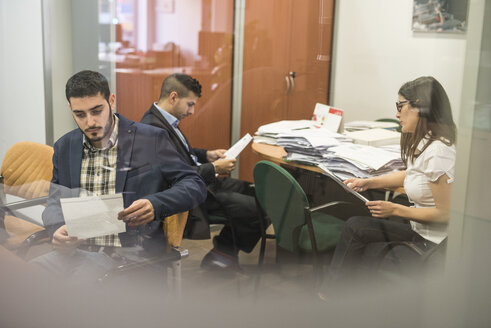 Two men and a woman reading documents in office - JASF000361